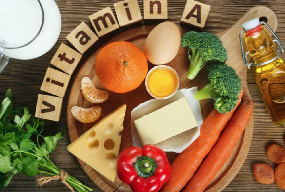 Vitamin A stock image with examples of orange, chees, capsicum, carrots, egg, olive oil, greens, buts, milk, and broccoli