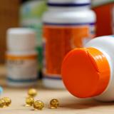 Vitamin tablets and pills on desk near medication bottles