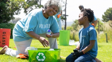 Senior woman volunteer collects recyclables with grandchild