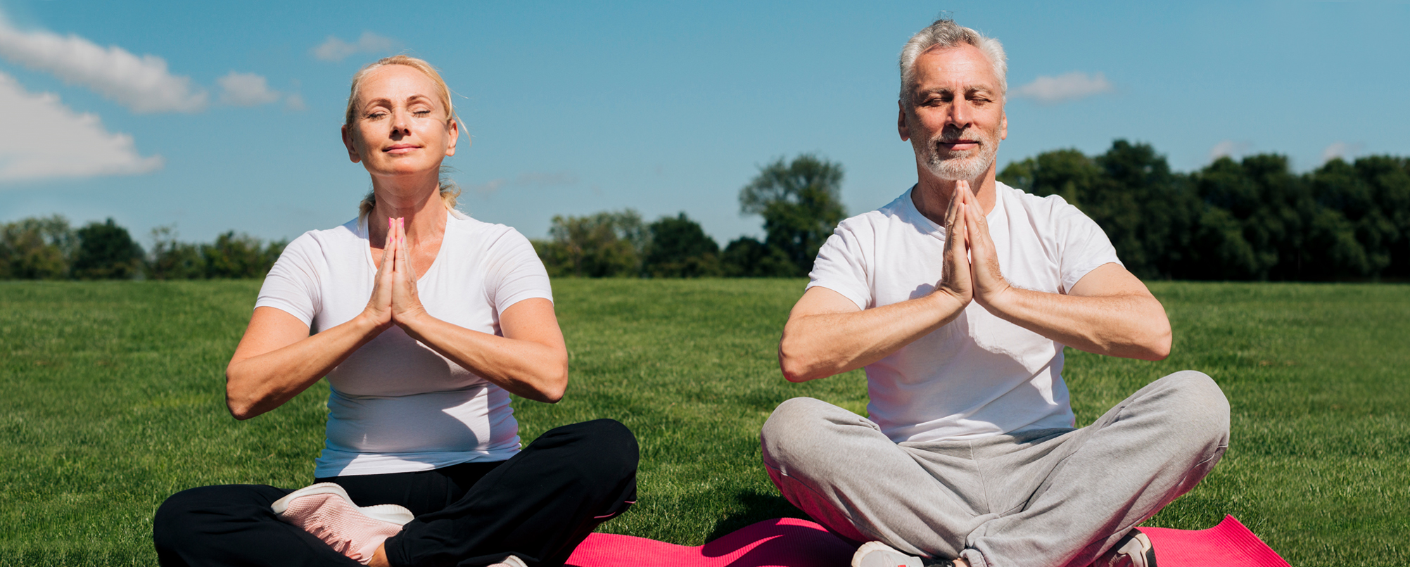 Senior couple practices yoga outdoors in city park.