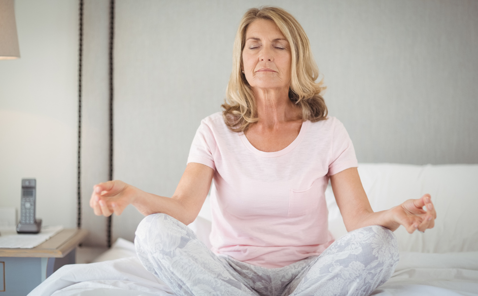 Senior woman practices yoga breathing exercises on bed