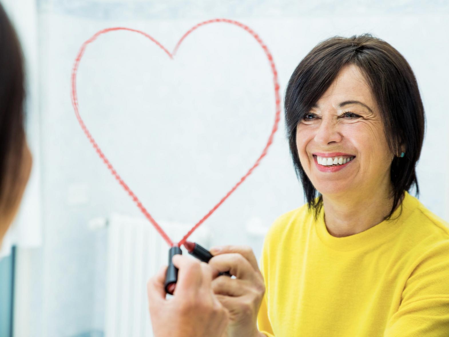 positive-senior-woman-drawing-heart-shape-on-the-m-C3Z8BVL