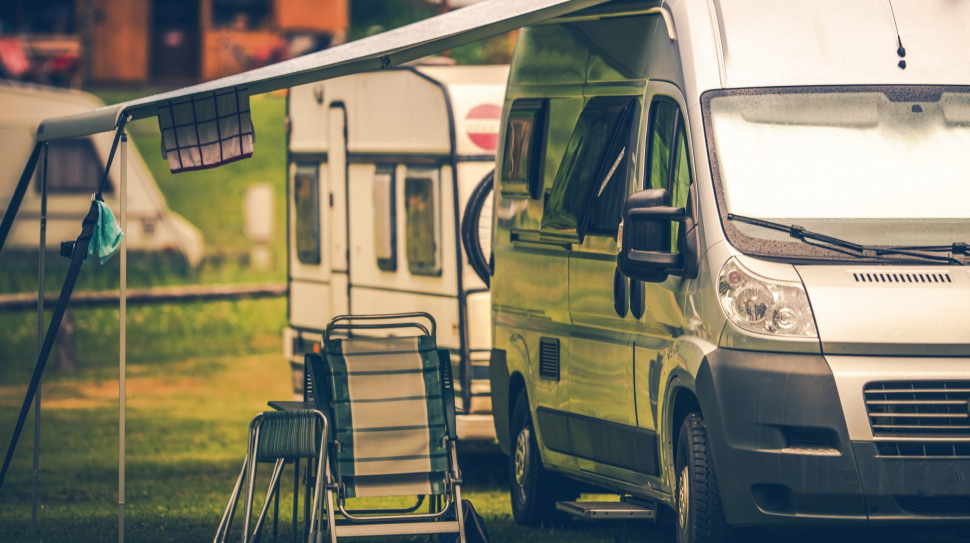 Motorhome Vacation Camping. Camper Van on the Campsite.