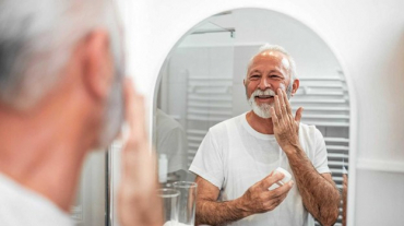 Senior applying face cream in the mirror