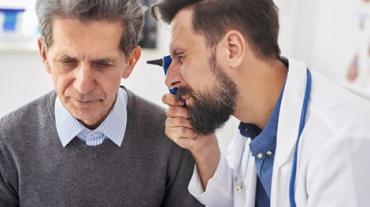 doctor inspecting a seniors ear