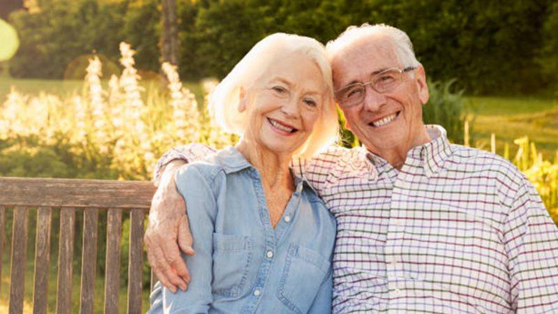 Seniors sitting on a park bench smiling