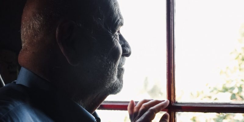 Senior looking out a window