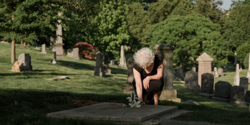 Senior standing over a grave