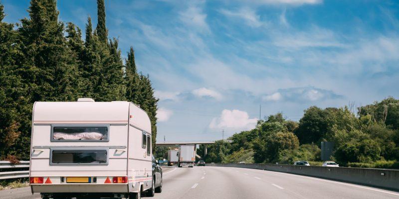 White Caravan Motorhome Car Goes On Highway Road.